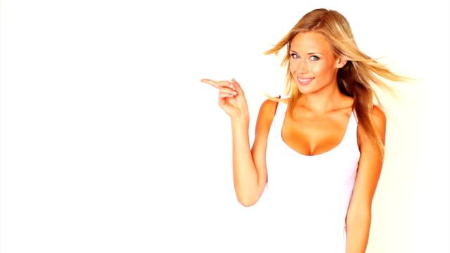 魅力的な若い女性の指を指すと笑顔 - 指差す 女性点の映像素材/bロール