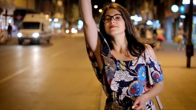 Attractive young woman raising her arm to call a taxi in a busy city at night video