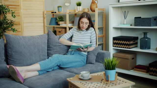 attractive young woman reading interesting book enjoying literature at home - book video stock e b–roll