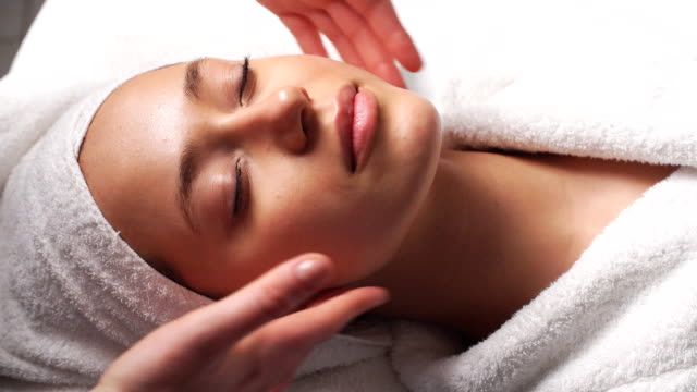 Attractive young woman receiving head massage at spa center Beautiful Young Woman Relaxing Female Receiving Facial Body Massage Beauty Spa spa treatment stock videos & royalty-free footage