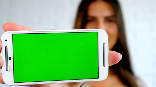 Attractive young woman showing smart phone with chroma-key, green screen video