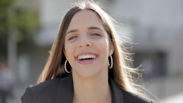 attraktive junge frau lächelt vor der kamera - ohrring stock-videos und b-roll-filmmaterial