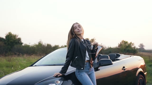 Attractive young woman standing near cabriolet