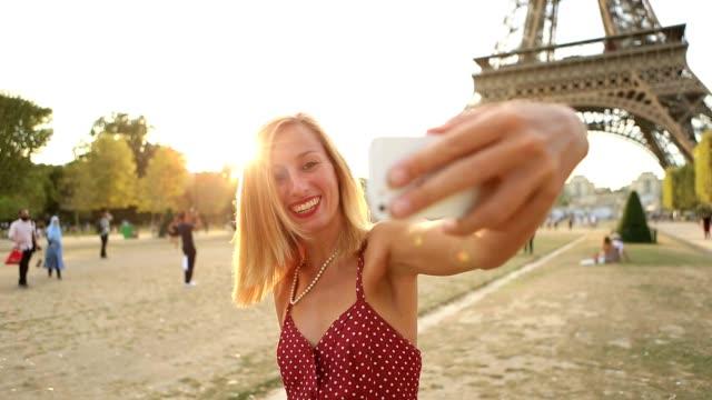 vídeos de stock, filmes e b-roll de mulher jovem e atraente leva selfie em paris - moda parisiense