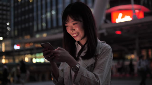 Attractive young woman using phone after work