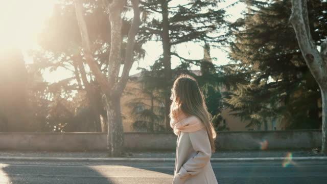 魅力的な若い女性が夕暮れの道の近くの公園でウォーキングします。明るい春の日を楽しんでいる女性は、街を探索します。 ビデオ