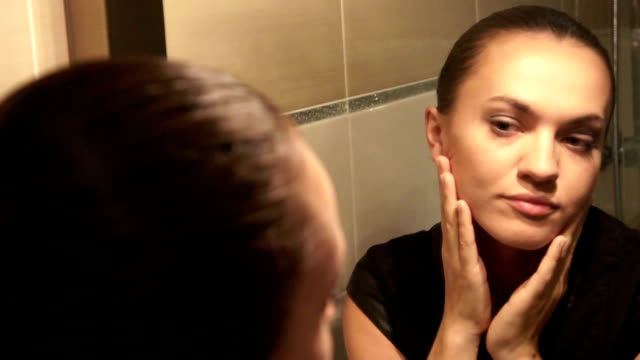 Attractive young woman watching her face in the mirror video