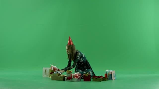 彼女のクリスマスの魅力的な若い女性は、背景にクロマキーをプレゼントします。 - サンタの帽子点の映像素材/bロール