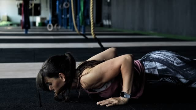 Attractive young woman with long hair doing pushups. Athlete woman indoors Attractive young woman with long hair doing pushups in gym. Close-up of muscular athlete woman indoors. Female doing push-ups push ups stock videos & royalty-free footage