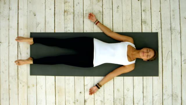 attraktiv ung kvinna träna hemma, gör yogaövning, liggande i shavasana liket eller döda kroppen utgöra, vila efter praktiken, mediterar, andning - zen bildbanksvideor och videomaterial från bakom kulisserna