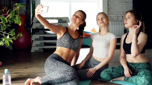 attraktiva unga kvinnor tar selfie efter yogaklass i ljusa moderna gym i hälsocentret. kvinnor bär trendiga sportkläder. sportutrustning i bakgrunden. - gym skratt bildbanksvideor och videomaterial från bakom kulisserna