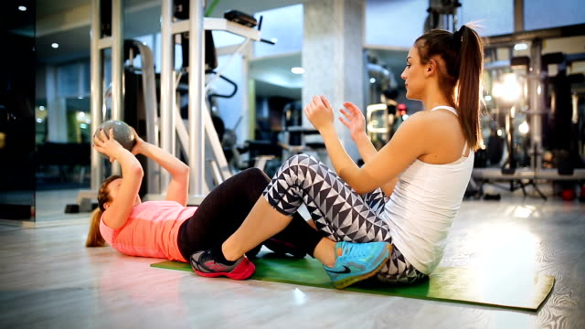 attractive young women exercising pilates with weight ball - donna forzuta video stock e b–roll