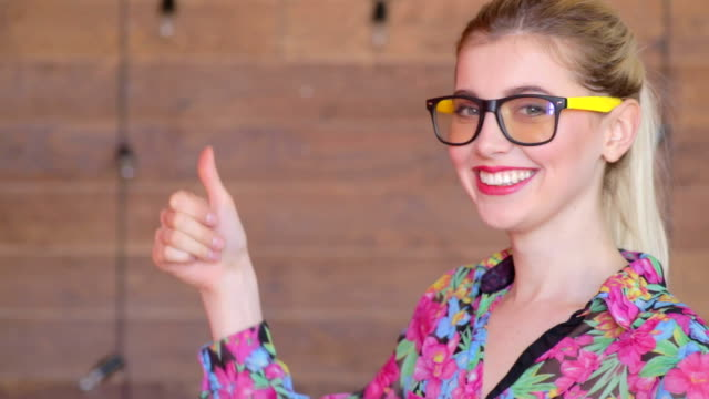Attractive young women in glasses smiles for camera and gives thumbs up video