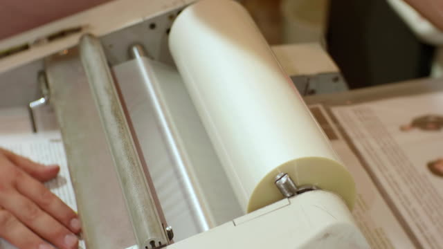 сaucasian male working with roll laminator - литография стоковые видео и кадры b-roll
