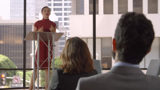 vídeos de stock e filmes b-roll de audience applaud young woman speaking at a business seminar - orador público
