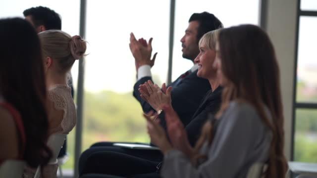 vídeos de stock, filmes e b-roll de público aplaudindo palestrante na sala de reunião do seminário de conferência - entrevista coletiva