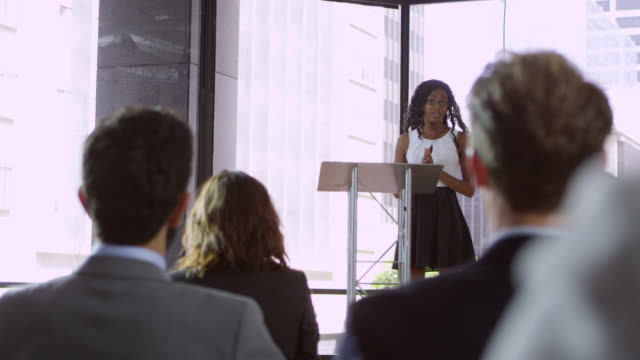 Audience at seminar applauding young black woman at lectern, shot on R3D video