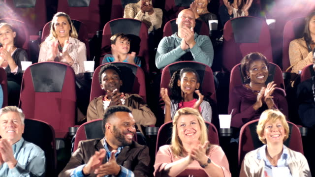 audience in movie theater start clapping - età miste video stock e b–roll