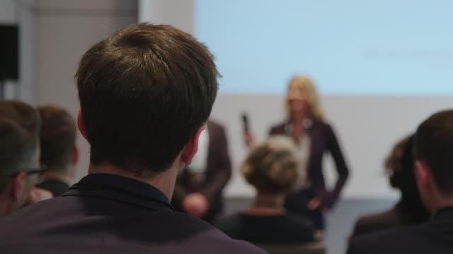 vídeos de stock e filmes b-roll de audience listening at business conference in hotel - orador público