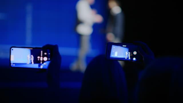 publikum verwendet smartphones, um zwei sprecher auf der bühne zu protokollieren, die auf der geschäftskonferenz sprechen. in audience hall public verwendet handys, um video von zwei star-moderatoren, live-event, tech-symposium zu schießen - zuschauerraum stock-videos und b-roll-filmmaterial