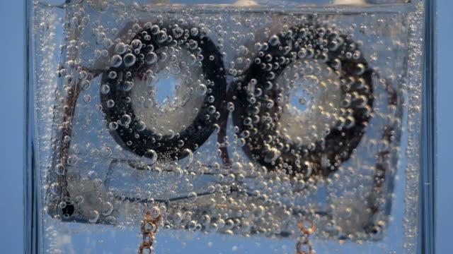 ljudkassett flyter i vatten med bubblor - chain studio bildbanksvideor och videomaterial från bakom kulisserna