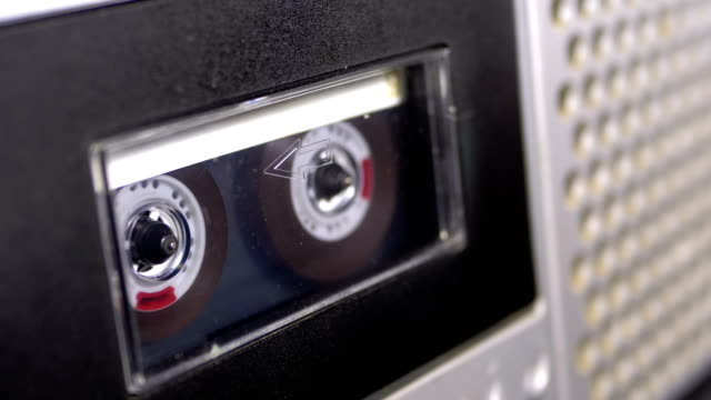 audio cassette is inserted into the deck of the audio tape recorder playing and rotates - cassetta video stock e b–roll