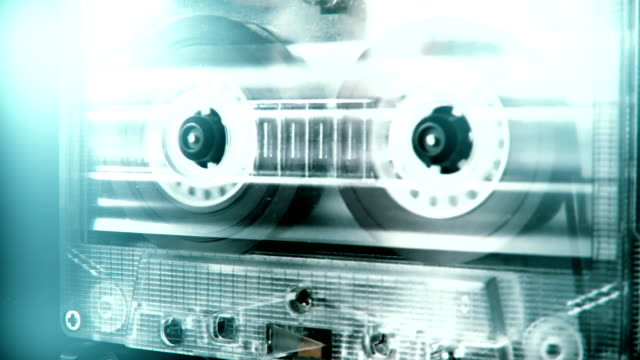 Audio cassette tape in use sound recording in the tape recorder. Vintage music cassette with a blank white label, playing back in the player. 4K, static camera shot