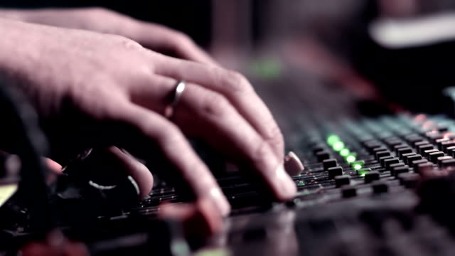 Audio Engineer adjusting faders on his mixing console desk during a live event. video