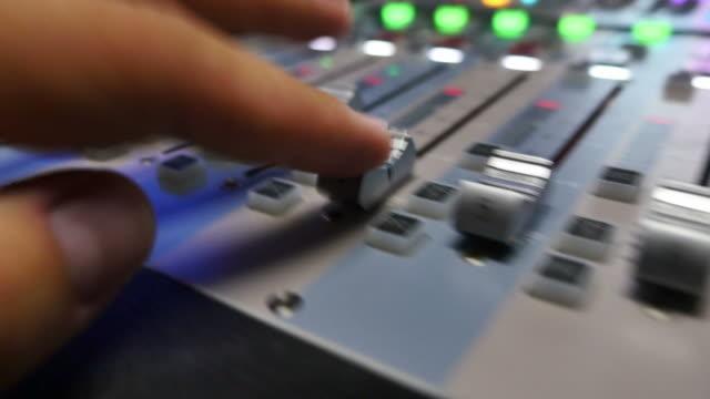 ljudmixer knoppar som dras snabbt med en person som arbetar i en studio - intoning bildbanksvideor och videomaterial från bakom kulisserna