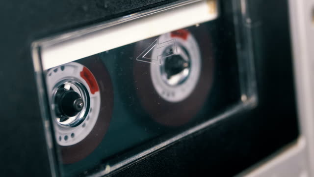 audio tape. vintage tape recorder plays audio cassette inserted therein - musicassetta video stock e b–roll