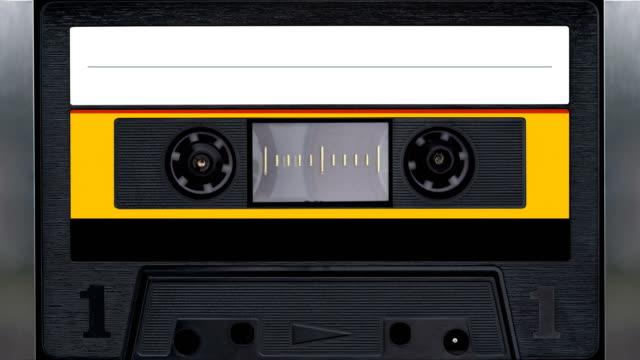 nastro magnetico. il registratore a nastro vintage riproduce la cassetta audio - disco audio analogico video stock e b–roll