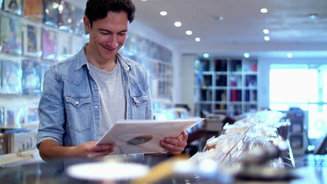 4K: Audiophile young man at record store video