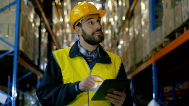stockvideo's en b-roll-footage met auditor draagt hard hat met tablet computer telt merchandise in magazijn. hij loopt door rijen van opslag rekken met merchandise. - checklist