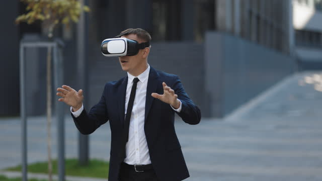 Augmented Reality. Businessman touch something using modern 3D vr glasses near office building. This new technology offers new 3D dimensions. Handsome man wearing virtual reality headset Augmented Reality. Businessman touch something using modern 3D vr glasses near office building. This new technology offers new 3D dimensions. Handsome man wearing virtual reality headset. businesswear stock videos & royalty-free footage