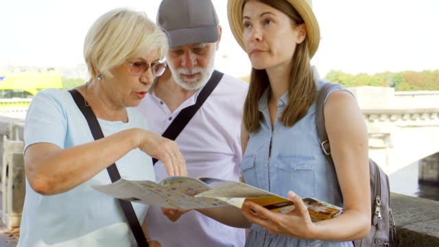 PARIS, FRANCE- CIRCA August 2017: Family enjoying vacation. Seniors and their daughter studying map video