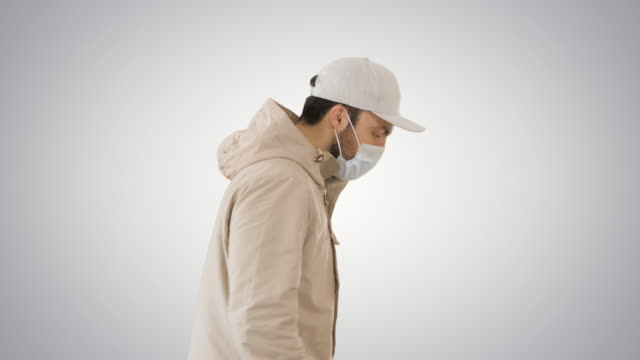 Ault man in jacket and in medical mask running on gradient background
