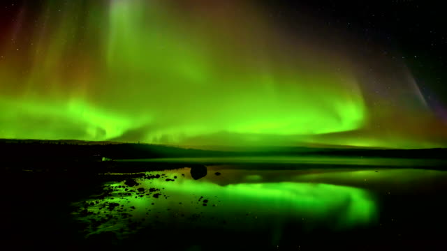 aurora borealis rolling over a lake - a time lapse video of layers of bright rolling northern lights reflecting in a rocky lake. - дикая местность стоковые видео и кадры b-roll