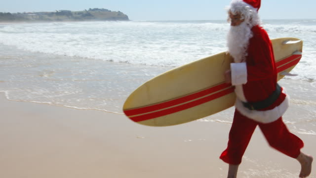 Australian Christmas Surfing Santa Claus Running on the Beach with a Surfboard Surfing Santa Claus running on the beach with a surfboard celebrating Christmas in Australia christmas fun stock videos & royalty-free footage