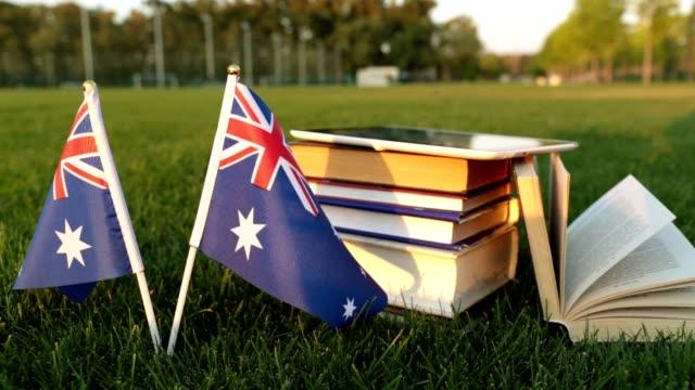 Drapeau australien et livres sur l'herbe. Éducation en Australie. - Vidéo