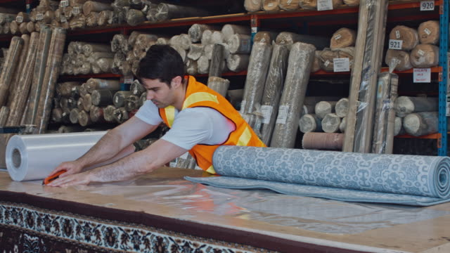 Australian male worker cutting plastic to wrap carpets at warehouse