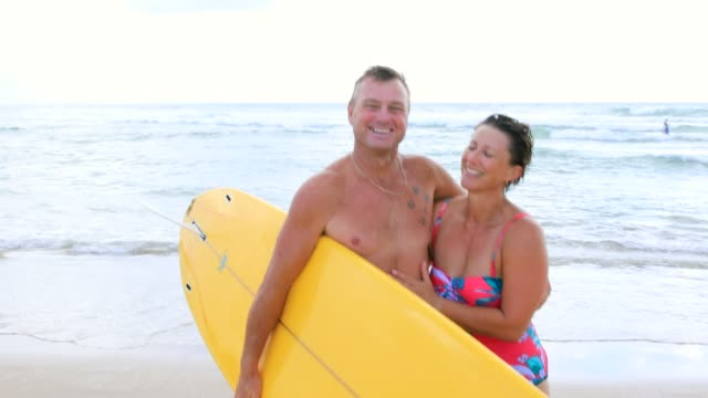 australian mature age surfing couple - baby boomer stock videos and b-roll footage