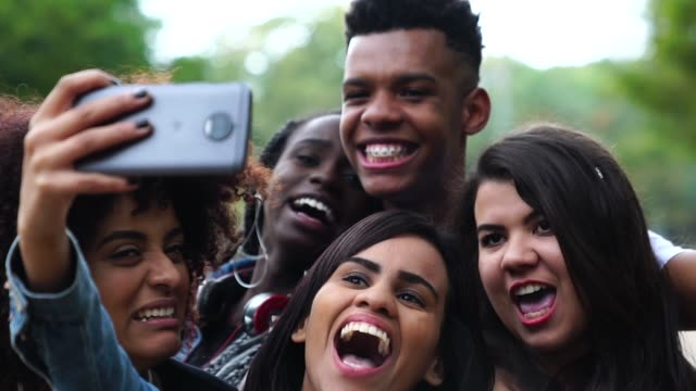 vídeos de stock, filmes e b-roll de autêntico grupo de diversos amigos tomando uma selfie no parque - povo brasileiro
