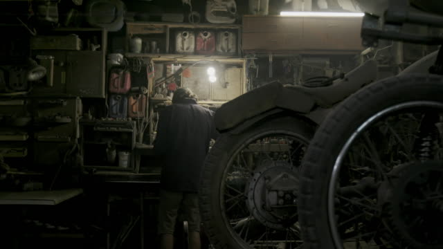 vídeos de stock e filmes b-roll de authentic motorcycle master works as a grinder in an old workshop against a background of vintage motorcycles - fundo oficina