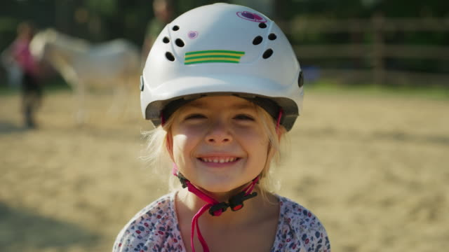 Authentic shot of a little girl with a jockey helmet smiling in the camera at riding stable on a sunny day