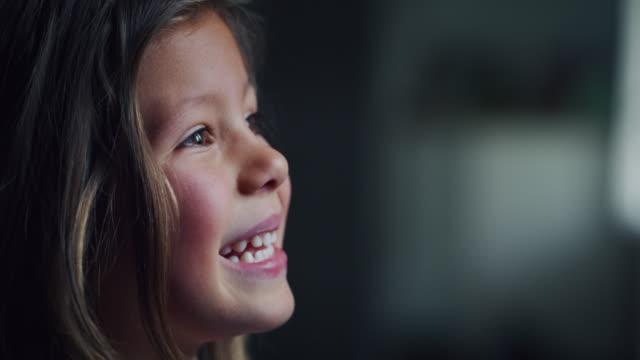 autentisk bild av söt liten flicka ser kasta fönstret med solen skiner - flickbaby bildbanksvideor och videomaterial från bakom kulisserna