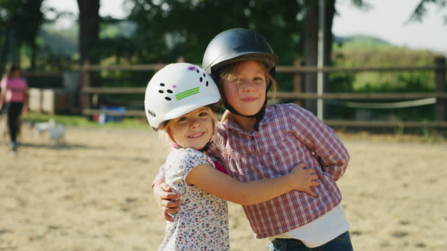 Authentic shot of two little girls with a jockey helmet  are smiling in the camera at riding stable on a sunny day