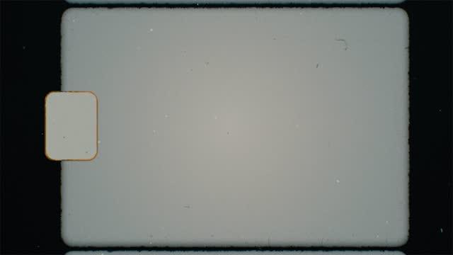 аутентичные super 8 фильм кадр сканирование с sprocket отверстие, утечки света и фильм зерновых накладок. для ретро винтажный вид. шум зерна и цара� - утечка света стоковые видео и кадры b-roll