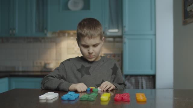 自閉症の少年は自宅でテーブルの上に色でプラスチック製のキャップを選別します。行にカラーキャップを選別自閉症の子供。自閉症で学ぶ。 - disabilitycollection点の映像素材/bロール