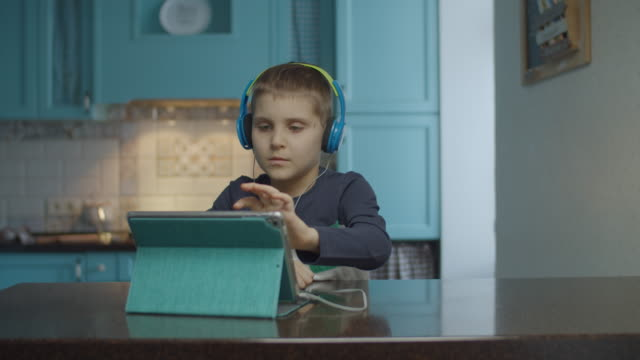 Autistic boy using tablet computer with headphones on the kitchen. Kid with autism looking around at home. Autism awareness Autistic boy using tablet computer with headphones on the kitchen. Kid with autism looking around at home. autism stock videos & royalty-free footage