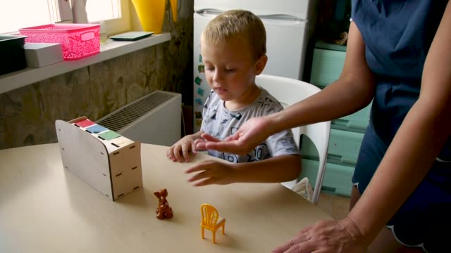 autistic picks items an autistic child tries to perform an assistant's task - to put a kitty on a chair autism stock videos & royalty-free footage